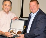 Rex Parrott, former Board Chairman, (left) receiving a gift of a gavel from current Chairman Don Plotts (right).